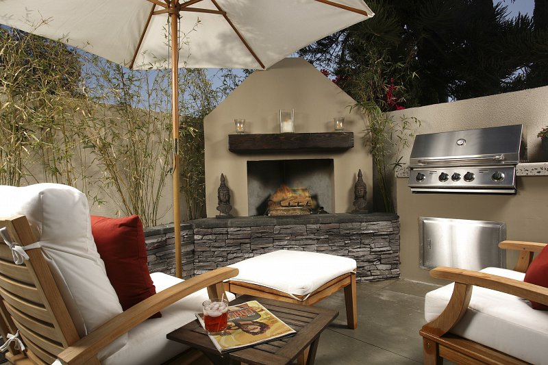 Outdoor patio including a fireplace and cooking area